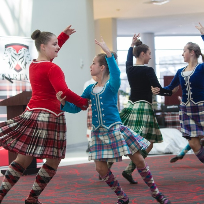 Eight girls dressed in plaid kilts dance with the Cincinnati Scots Highland dancers