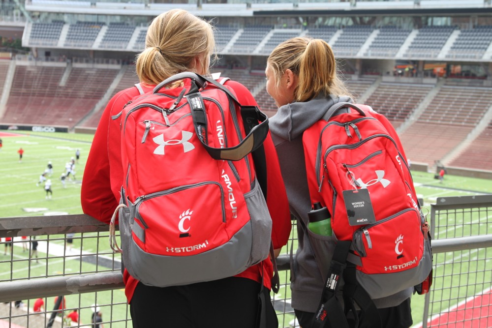 Two women UC soccer players stand in Nippert Stadium wearing UC Under Armour red backpacks