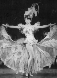 Faith poses in an elegant dancing dress, arms holding the giant skirt out to her sides.