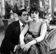 Theda Bara sits in a chair while a gentleman in a suit swoons over her shoulder.