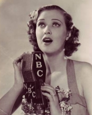 Jane sings a song into an NBC microphone.