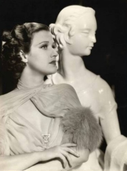 Jane poses next to a white bust. She wears a flowing, yet classic, gown.