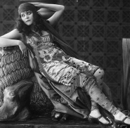 Theda stretches out while wearing an elegant mid-Eastern outfit.