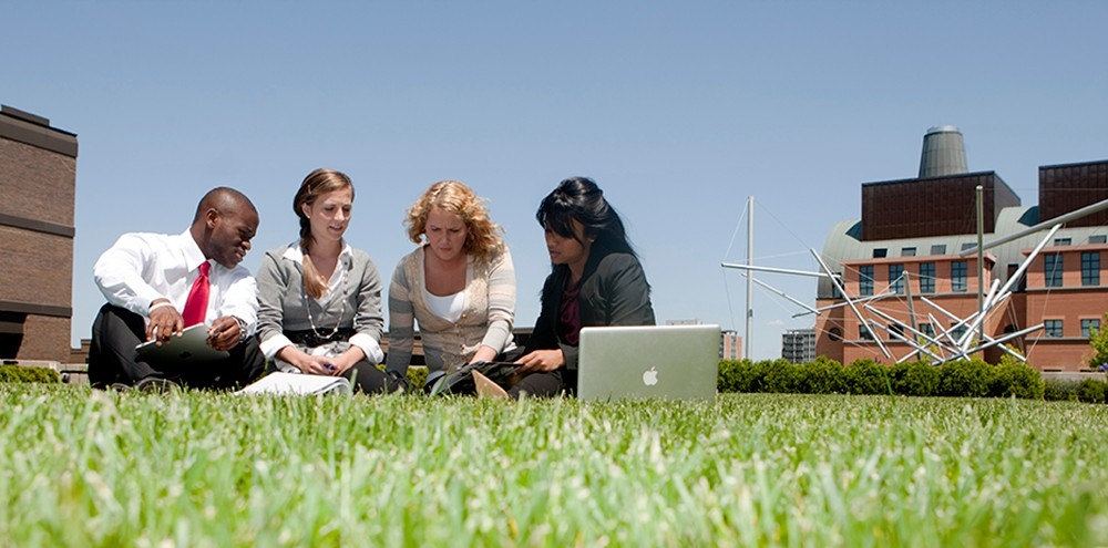 Students review textbooks on campus lawn