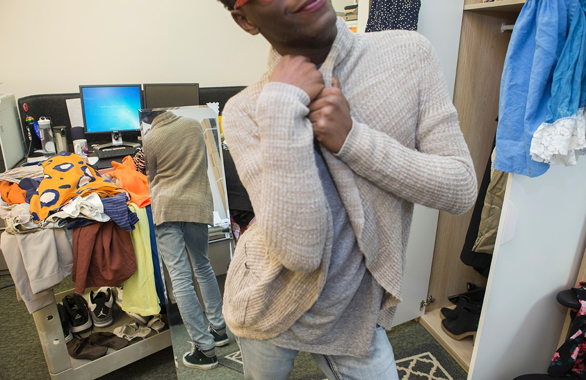 A student tries on a sweater before a mirror.