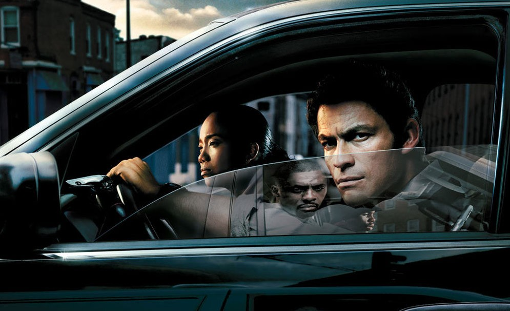 In an image from The Wire, Jimmy McNulty (Dominic West) and Kima Greggs (Sonja Sohn) sit in a car with a reflection of Stringer Bell (Idris Elba) in the window.