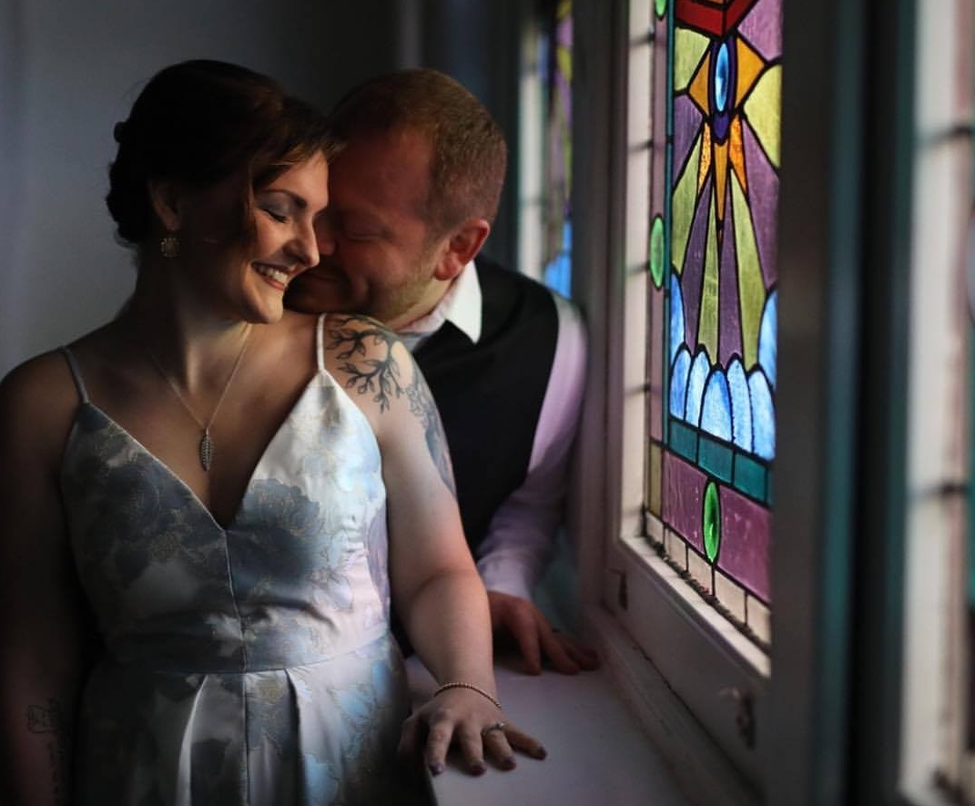 Tori and Nelson Thomas near a stained glass window soon after their wedding.