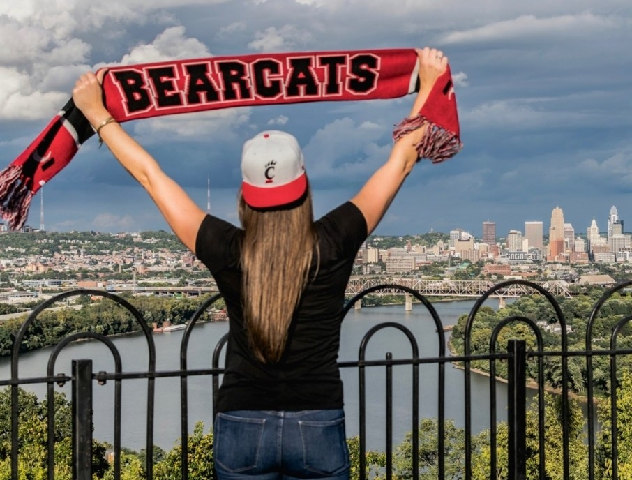 A UC Bearcats fan holds up a red and black scarf with BEARCATS written in large block letters