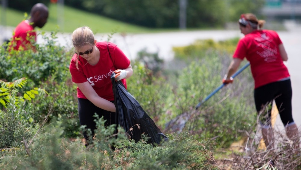 woman stands stuffing dead weeds into a black garbage bag
