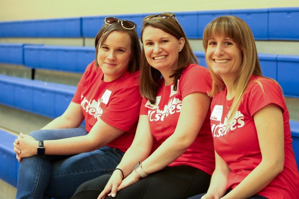 Three UC Serves volunteers watch a dance display from bleachers at John P. Parker Elementary School on UC Serves Day.