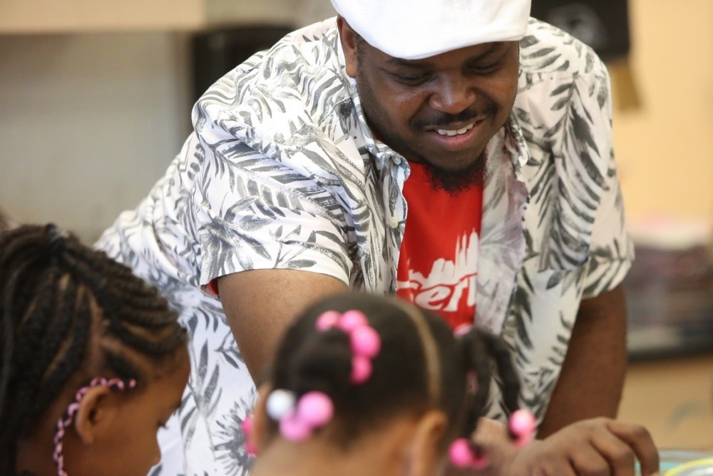 UC Serves volunteer helps children make tie-dye T-shirts on UC Serves Day.