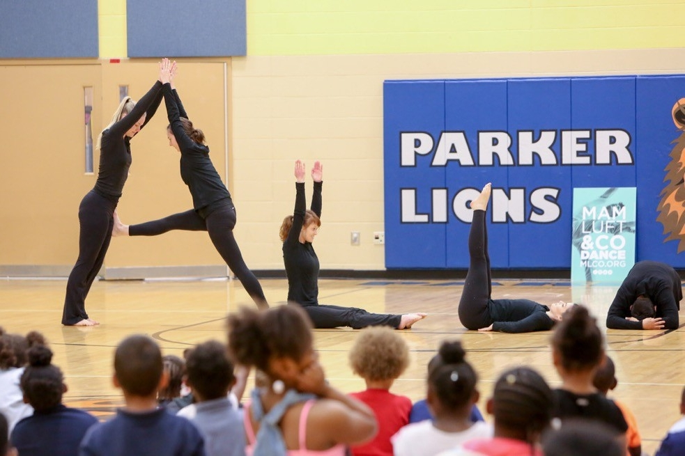 Mamluft & Co. dance team stands in the formation of alphabet letters that spell ALL for students in John P. Parker Elementary School on UC Serves Day.