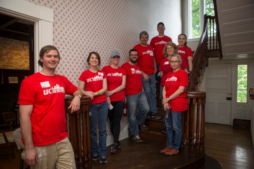 Group of UC Serves volunteers stand on a stairway inside Cincinnati's Harriet Beecher Stowe House on UC Serves Day.