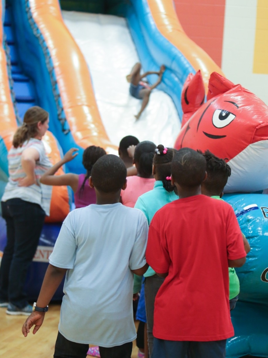 UC Serves volunteer stands at a large inflatable with school children on UC Serves Day.