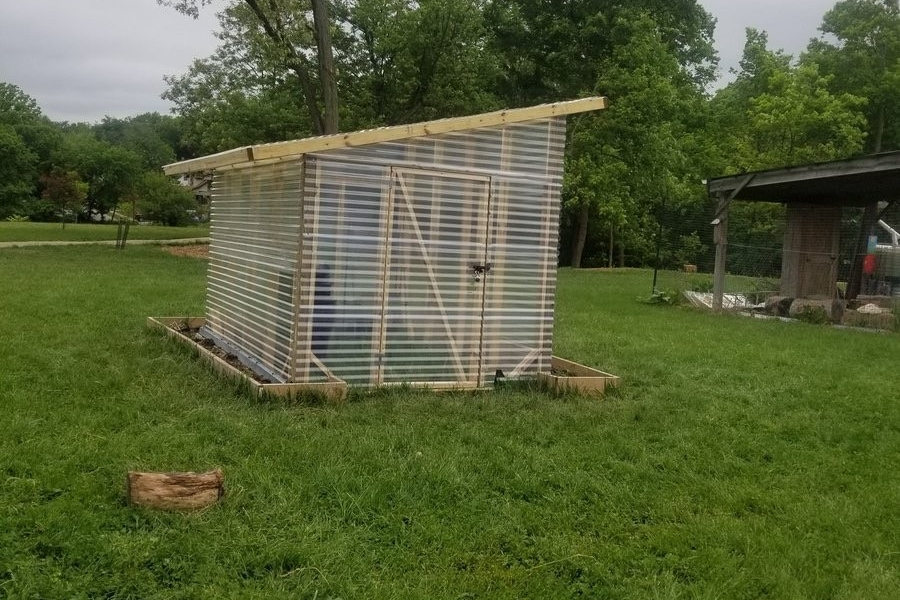 A completed greenhouse built by UC Serves volunteers stands proudly on a grassy area.