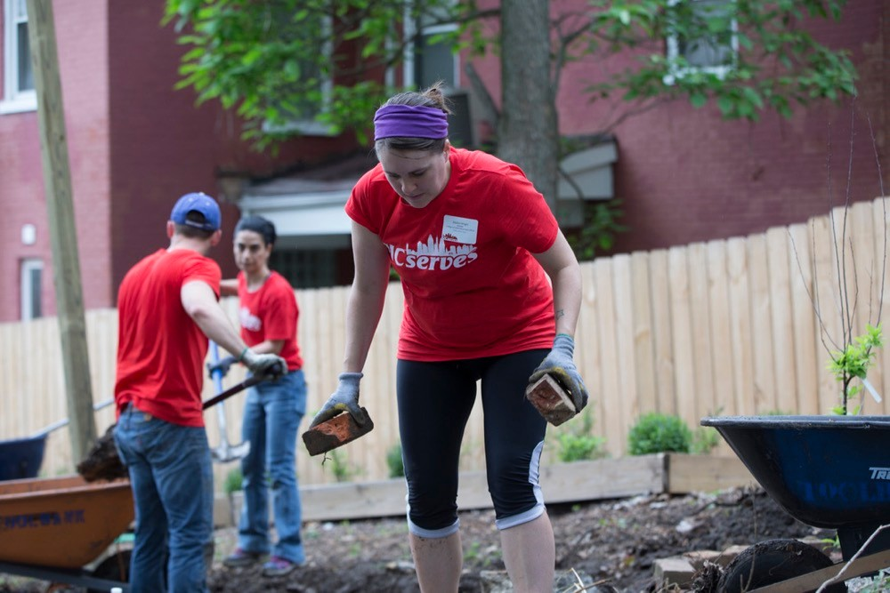 UC Serves volunteers hold bricks and shovels in an urban garden on UC Serves Day. photo/Joseph Fuqua II/UC Creative Services