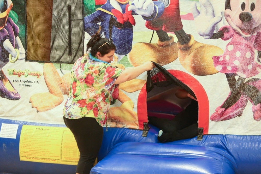 UC Serves volunteer stands at the entryway of an large bouncy inflatable to let kids in and out on UC Serves Day.