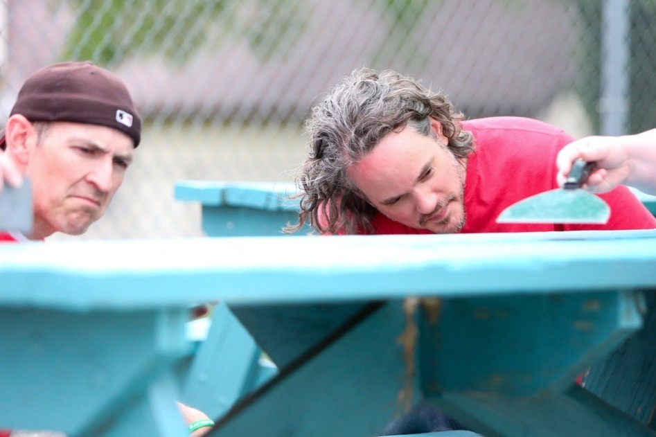 Two UC Servers watch closely as they paint a picnic table at the Gamble Nippert YMCA on UC Serves Day.