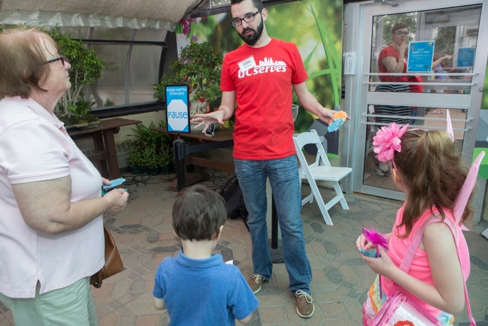 A UC Serves volunteer hands tickets to a family at Cincinnati's Krohn Conservatory Butterfly exhibit.
