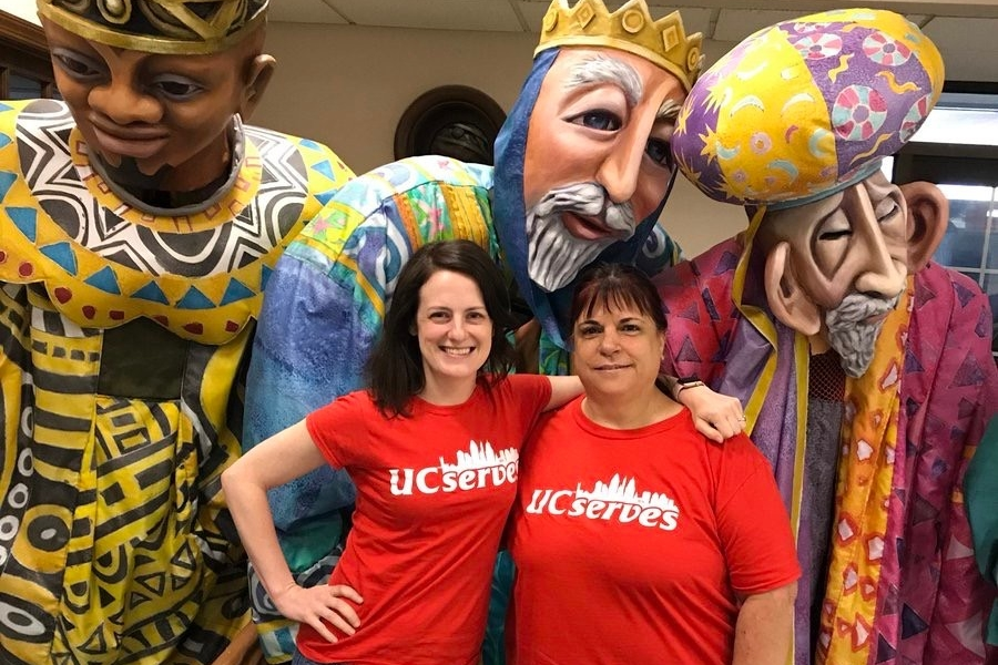 Two UC Serves volunteers stand in front of three larger-than-life puppet costumes at Cincinnati's Madcap Puppets on UC Serves Day.