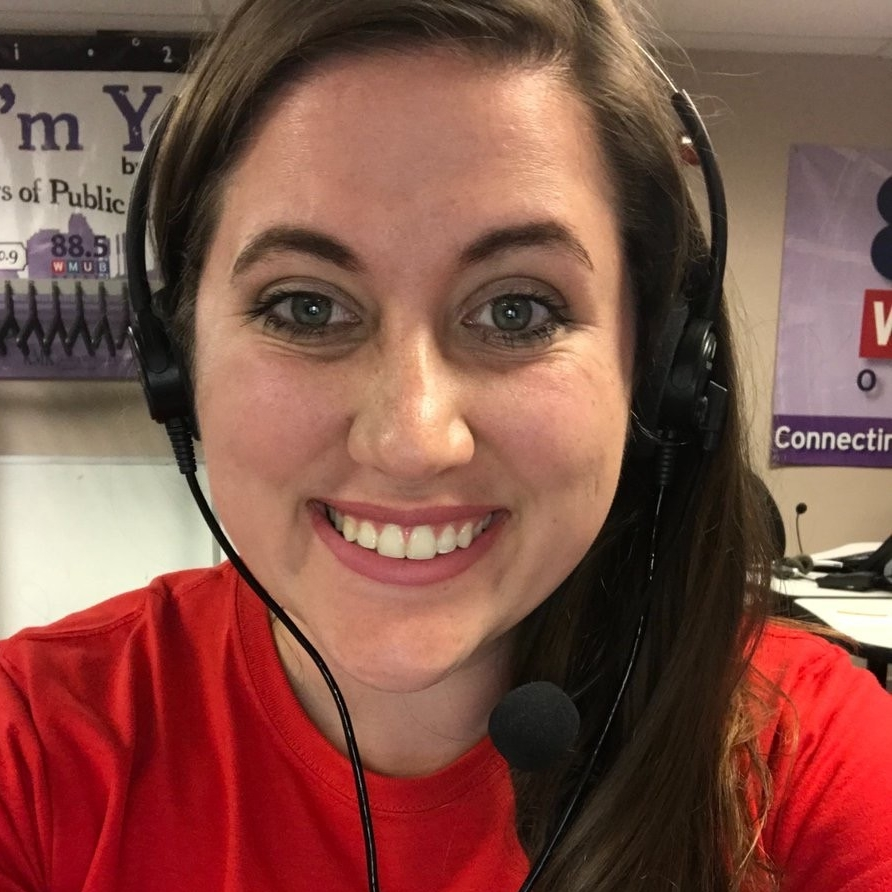 UC's Lacey Tomlinson wears a headset while answering pledges for WVXU.