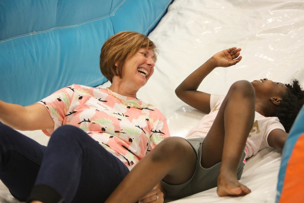 Lisa Ventre, director of photography in UC Creative Services slides down an inflatable slide with an elementary student on UC Serves Day.