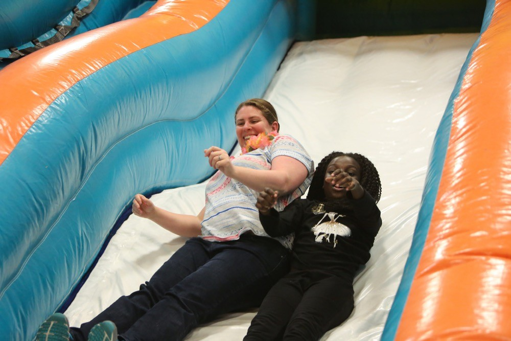 UC Serves volunteer Jessica Phillips of UC Finance slides down an inflatable slide with an elementary student on UC Serves Field Day.