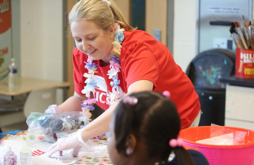 UC Serves volunteer helps children at Woodford Paideia Elementary School create tie dye T-shirts during their field day event.