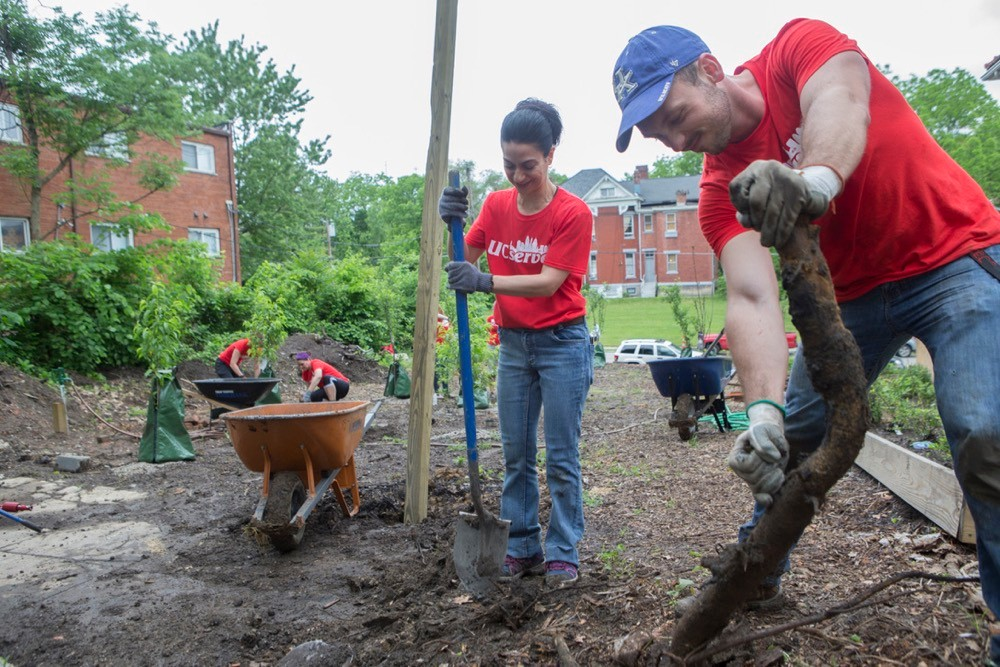 UC Serves volunteers wearing red T-shirts stand with tools and shovels ready to clear an overgrown lot.