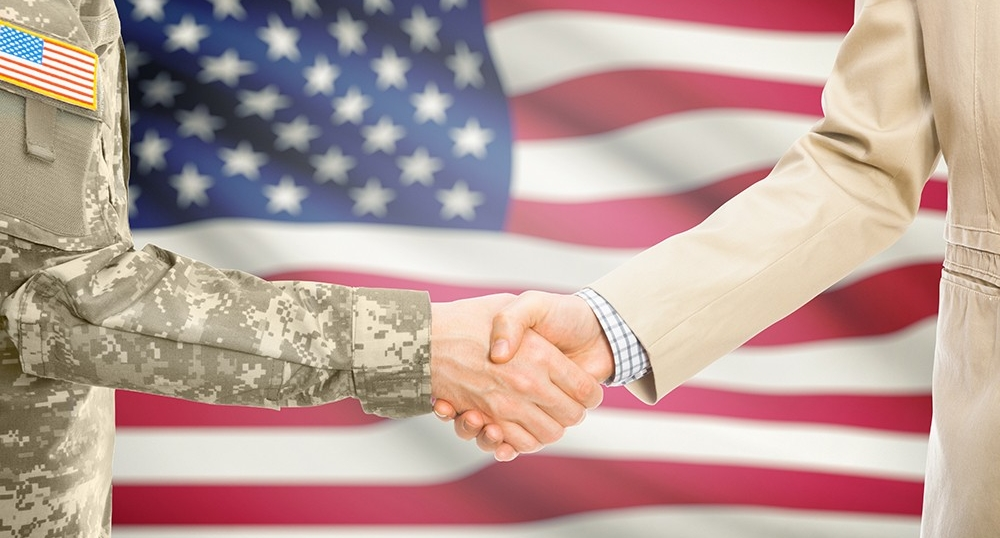 A soldier shakes hands with a man in a business suit in front of an American flag