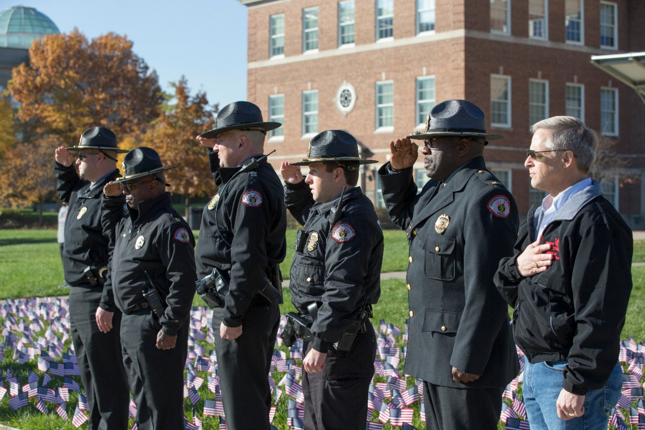 The UC Police Department command staff salutes.