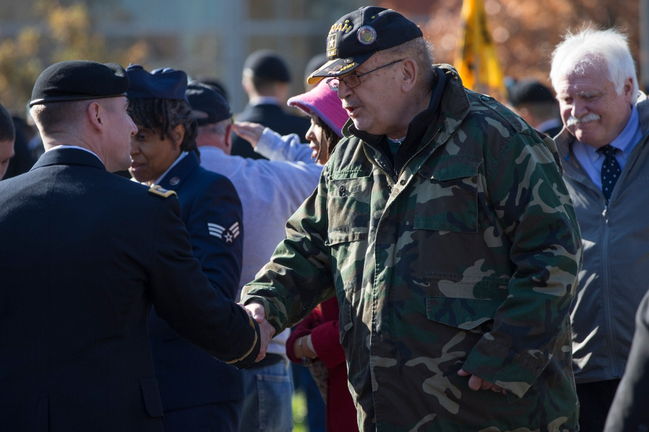 A male uniformed soldier shakes hands with a male attendee wearing a camouflage jacket.