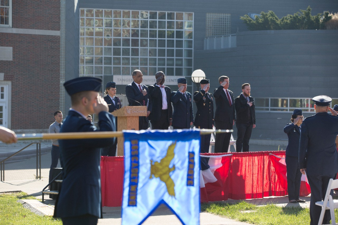 The distinguished speakers stand and salute for the National Anthem.