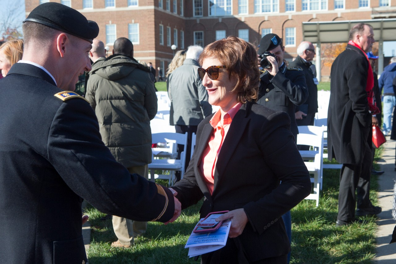 A uniformed male soldier shakes a woman's hand.