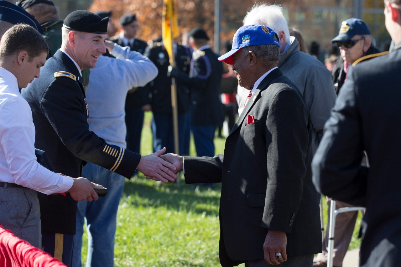 A veteran wearing a blue baseball hat and a suit is given a coin commemorating this year's Veterans Day ceremony.