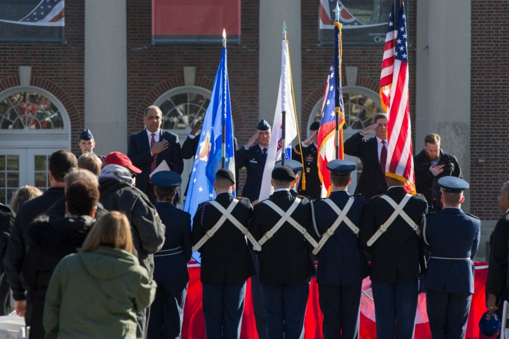 UC President Neville Pinto and others in attendance stand as an ROTC color guard presents colors at Thursday's UC Veterans Day Ceremony.