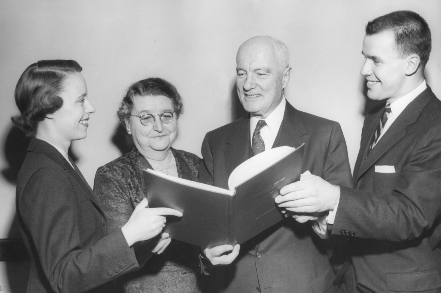 From the left: Shirley Parsons, Mrs. Raymond Walters, Dr. Raymond Walters, Otto Budig. The Walters are presented with a signature book at Raymond Walters' student-sponsored retirement dinner in 1955.