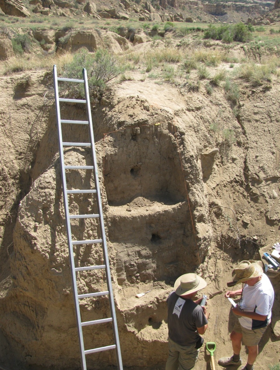 UC professors Lewis Owen and Ken Tankersley stand near a ladder colleting underground soil samples in Chaco Canyon, New Mexico.