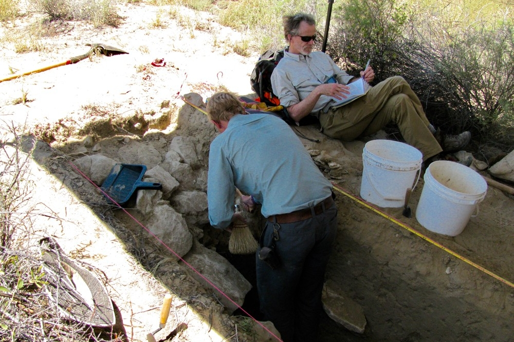 UC graduate student Jon-Paul McCool has back turned as he excavates a berm wall of an ancient canal as UC Professor Christopher Carr sits in the shade taking notes.