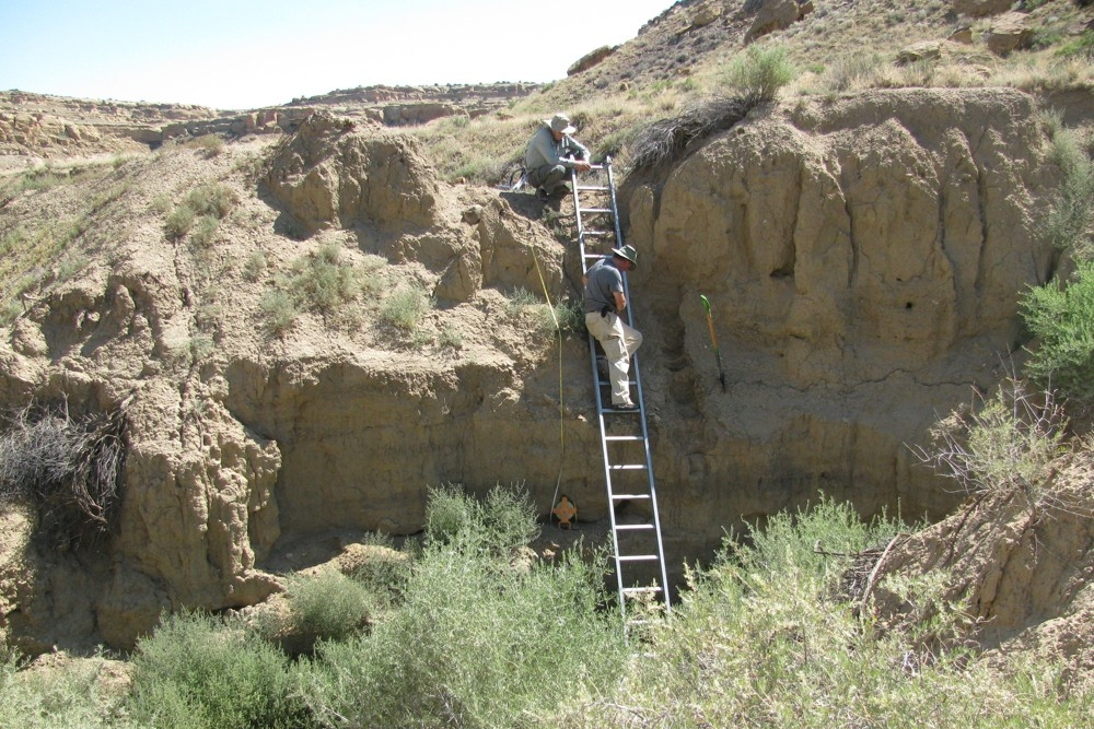 UC professors Nick Dunning (on ladder) and Vern Scarborough (top of ladder) record data from ancient pueblo ruins in Chaco Canyon, New Mexico.