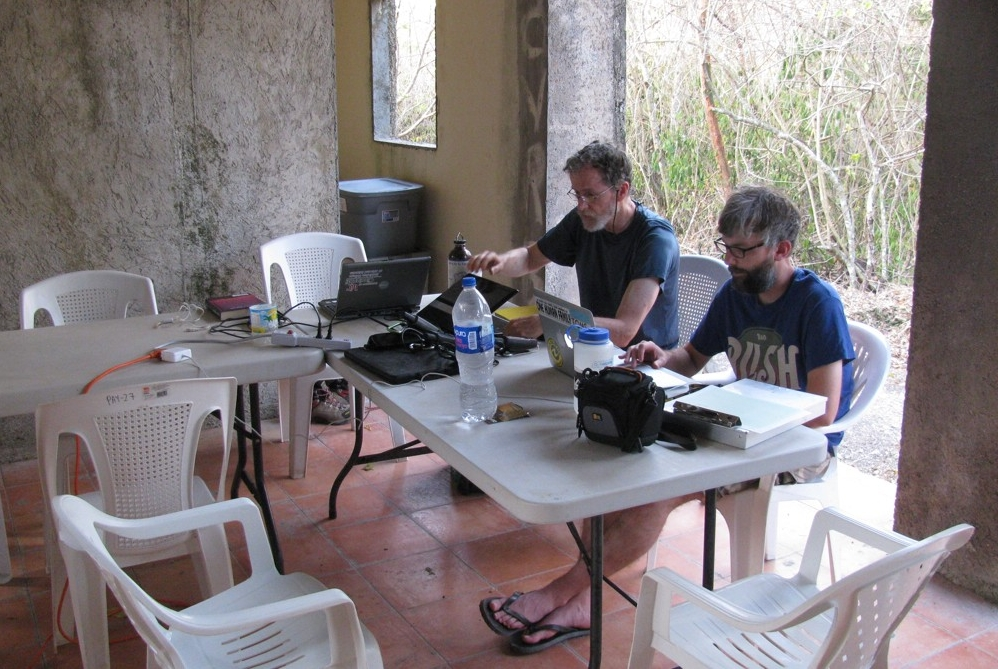 UC researchers sit at a table taking notes in the shade at the Yaxnohcah excavation camp in Central America.