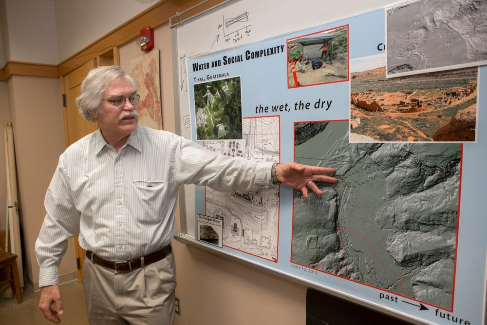 UC anthropology professor Vern Scarborough points to a poster of aerial views of ancient Tikal and Chaco Canyon.