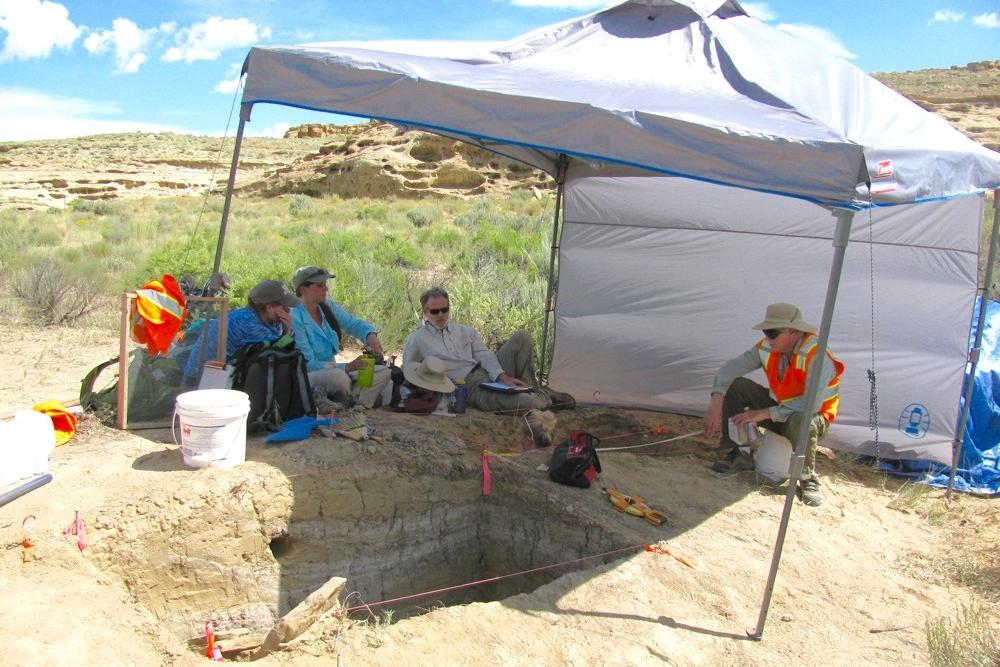 UC researchers sit under a tent-covered excavation site in Chaco Canyon, New Mexico.