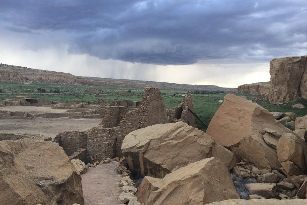 Large boulders and rough landscape with stormclouds overhead in Chaco Canyon, New Mexico.