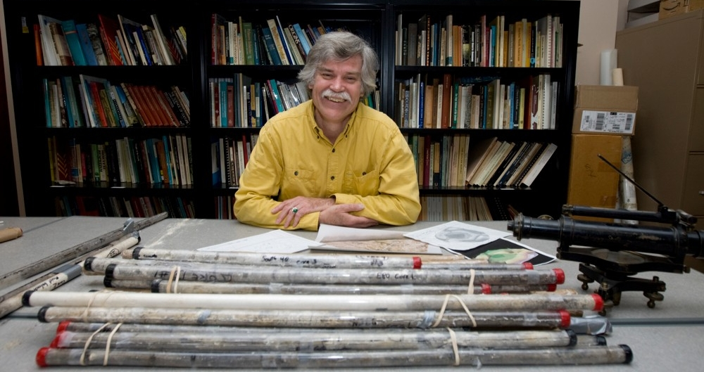 UC anthropology professor, Vern Scarborough sits at table with tubes of dirt and rock in front of him.