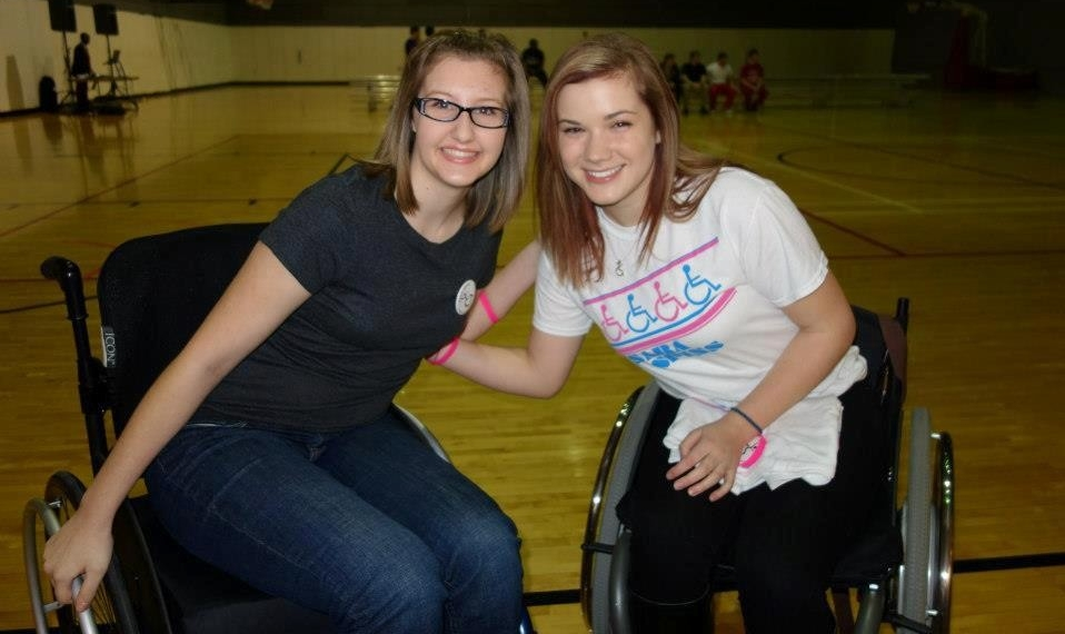 Abbey Hunter and Sara Whitestone pose for a photo in their wheelchairs inside the Campus Recreation Center gymnasium.