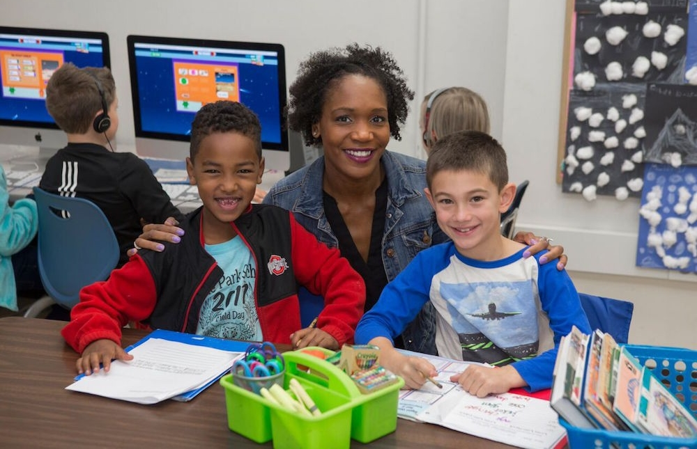 UC almuna and Olympian Mary Wineberg poses for a picture in her class at Cincinnati public school Hyde Park Elementary with two students.