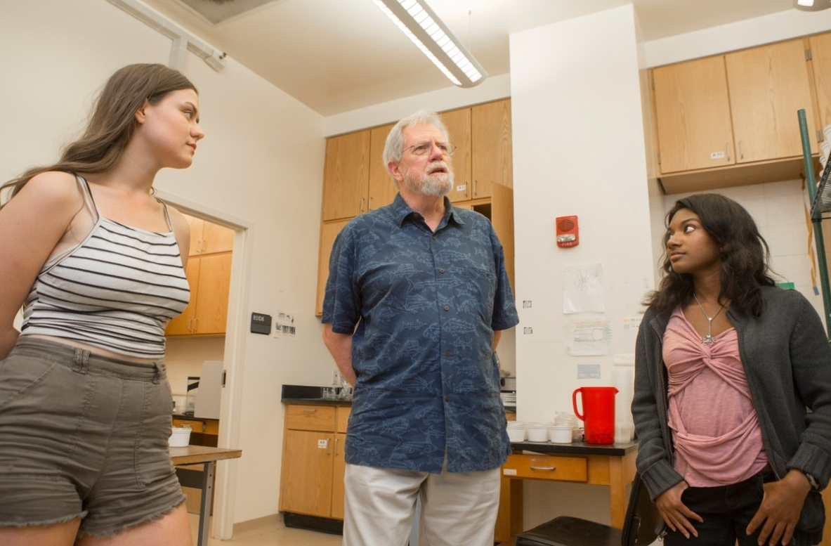 UC biology professor George Uetz, center, talks about his spider research with biology students Olivia Bauer-Nilsen, left, and Trinity Walls.