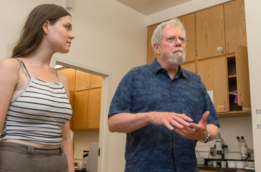 UC biology student Olivia Bauer-Nilsen, left, and UC biology professor George Uetz talk about research they presented this year at the American Arachnological Society's meeting.