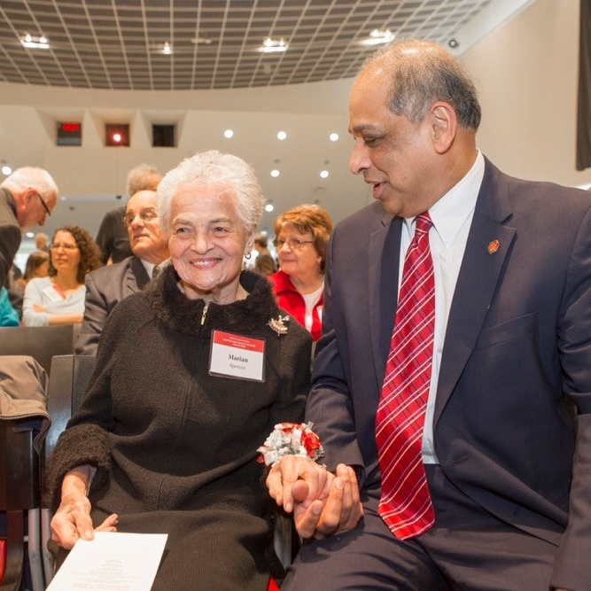 Marian Spencer holds UC President Neville Pinto's hand at an award ceremony. photo/Joseph Fuqua II/UC Creative Services